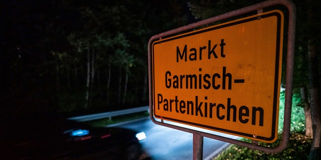 In this Sept. 13 photo, a car drives past the place name sign in Garmisch-Partenkirchen, Germany. Officials in southern Germany are considering imposing hefty fines against a 26-year-old American woman linked to a cluster of coronavirus cases in the Alpine resort town of Garmisch-Partenkirchen, including at a hotel that caters to U.S. military personnel. (Lino Mirgeler/dpa via AP)