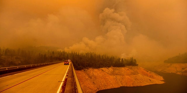 A plume rises from the Bear Fire as it burns along Lake Oroville on Wednesday, Sept. 9, 2020, in Butte County, Calif.