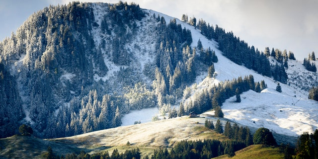 Fresh snow is visible on the slopes of the Moleson mountain near the still green pastures, on Saturday, 26 September 2020, at Moleson in Gruyere, Switzerland.