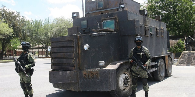 FILE PHOTO - Soldiers stand guard in front of a modified and armored truck as it is displayed to the media at a military base in Reynosa, in the Mexican state of Tamaulipas June 5, 2011. Soldiers seized a couple of modified and armored trucks at a warehouse in the municipality of Camargo during a patrol on Saturday, local media reported. According to the military, the vehicles were used by the CDG (Gulf Cartel) to transport drugs and hitmen.