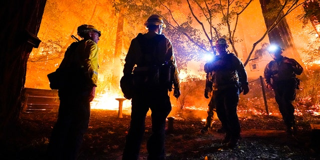 Firefighters make a stand in the backyard of a home in front of the advancing CZU August Lightning Complex Fire Friday, Aug. 21, 2020, in Boulder Creek, Calif.