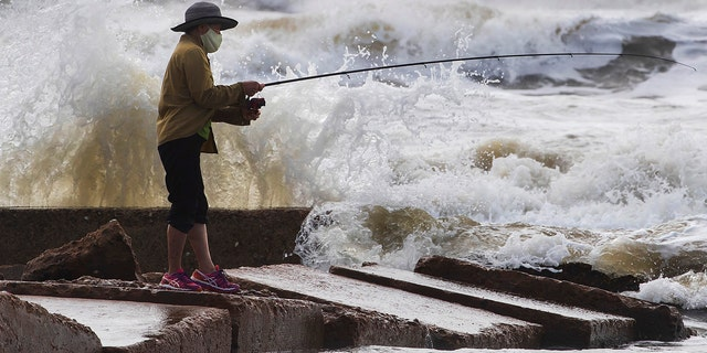 Waves crash as Houston resident Tinh Pham fishes from the rocks at Diamond Beach on the west end of the Galveston Seawall in Galveston, Texas on Saturday, Sept. 19, 2020.