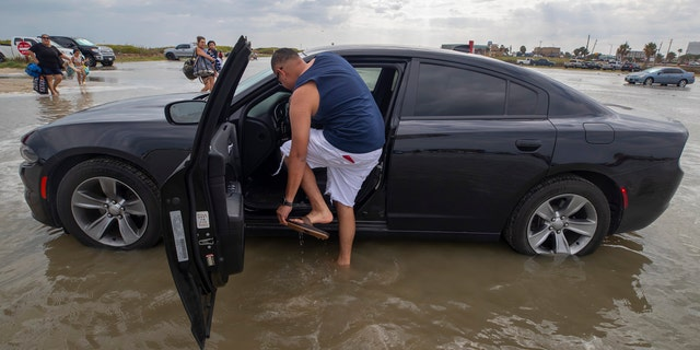 Houston resident Lupe Don removes his flip-flops while moving his car from the flooding Stewart Beach parking lot in Galveston, Texas on Saturday, Sept. 19, 2020.