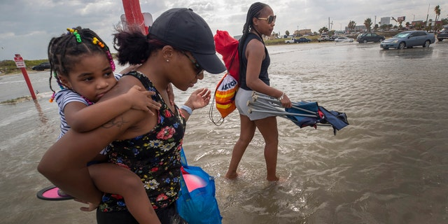 Stacey Young gives her daughter, Kylee Potts, a piggyback ride across the flooding Stewart Beach parking lot in Galveston, Texas on Saturday, Sept. 19, 2020.