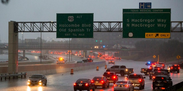 Cars turn around on southbound 288 because of a road blockage caused by Tropical Storm Beta flooding Tuesday, Sept. 22, 2020, in Houston.