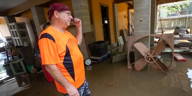 Lance Lindsley stands in the flooded garage of his house on Appleblossom Lane in Friendswood, Texas on Tuesday, Sept. 22, 2020, following Tropical Storm Beta.