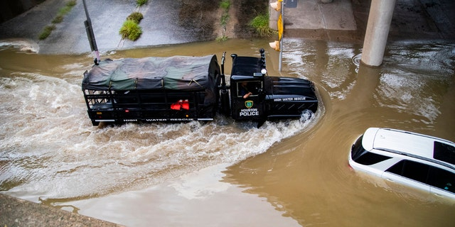 A Houston Police Water Rescue vehicle mobilizes by a stranded by flood car on Houston Ave., during Tropical Storm Beta, Tuesday, Sept. 22, 2020, in Houston.