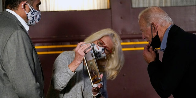 Franco Harris, former player for the Pittsburgh Steelers football player, left, looks on as his wife Dana Dokmanovich holds a screen so that Democratic presidential candidate former Vice President Joe Biden can chat with Joanne Rogers virtually at Amtrak's Latrobe Train Station, Wednesday, Sept. 30, 2020, in Latrobe, Pa. Joanne Roger is Fred Rogers' widow who was known as Mister Rogers. (AP Photo/Andrew Harnik)