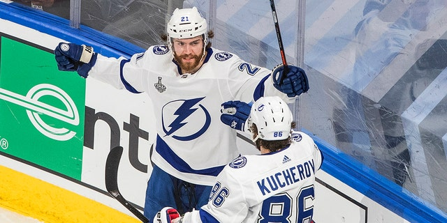 Tampa Bay Lightning center Brayden Point (21) celebrates his goal against the Dallas Stars with Nikita Kucherov (86) during the second period of Game 4 of the NHL hockey Stanley Cup Final, Friday, Sept. 25, 2020, in Edmonton, Alberta. (Jason Franson/The Canadian Press via AP)