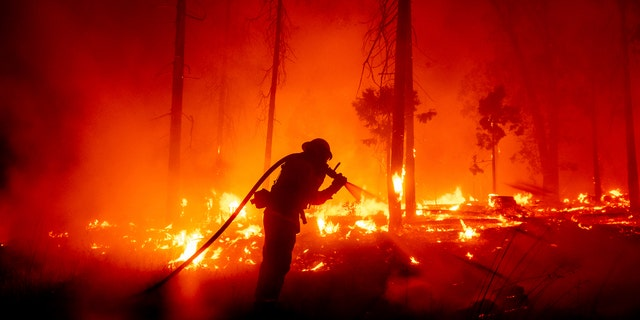 In this Sept. 7, 2020, file photo, a firefighter battles the Creek Fire as it threatens homes in the Cascadel Woods neighborhood of Madera County, Calif.