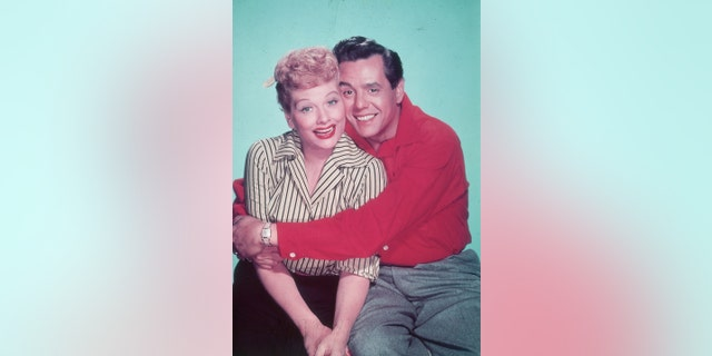 Circa 1955: Studio portrait of American actor and comedian Lucille Ball receiving a hug from her husband, Cuban-born bandleader and singer Desi Arnaz, against a green backdrop.