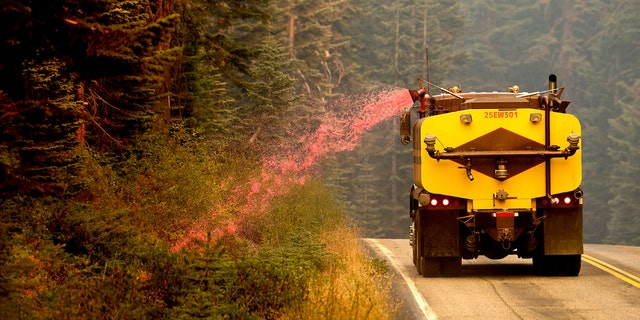 A truck sprays fire retardant on vegetation to help stop the spread of the North Complex Fire in Plumas National Forest, Calif., on Monday, Sept. 14, 2020.