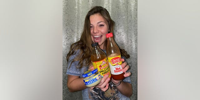 TikTok user Cammie Cooke poses with garlic, apple cider vinegar and hot sauce for her COVID food review. (Cammie Cooke)
