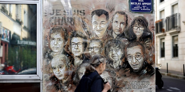 A woman walks past a painting by French street artist and painter Christian Guemy, known as C215, in tribute to members of Charlie Hebdo newspaper who were killed by jihadist gunmen in January 2015. (THOMAS COEX/AFP via Getty Images)