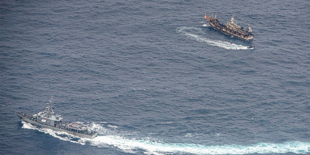 Ecuadorian Navy vessels surround a fishing boat after detecting a fishing fleet of mostly Chinese-flagged ships in an international corridor that borders the Galapagos Islands' exclusive economic zone, in the Pacific Ocean, August 7, 2020. Picture taken August 7, 2020. REUTERS/Santiago Arcos - RC2EAI9QEFR7