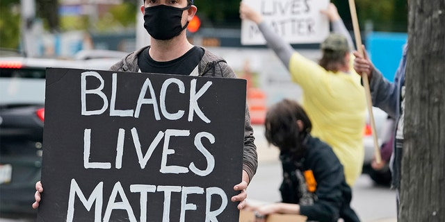 A protester holds up a Black Lives Matter sign near the debate hall, 星期二, 九月. 29, 2020, in Cleveland. The first presidential debate between Republican candidate President Donald Trump and Democratic candidate and former Vice President Joe Biden is being held in Cleveland Tuesday. (AP Photo/Tony Dejak)