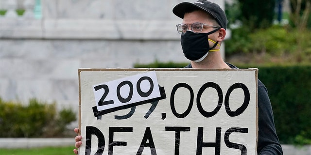 A man holds up a sign on the coronavirus deaths in America at a rally near the debate hall, 星期二, 九月. 29, 2020, in Cleveland. The first presidential debate between Republican candidate President Donald Trump and Democratic candidate and former Vice President Joe Biden is being held in Cleveland Tuesday. (AP Photo/Tony Dejak)
