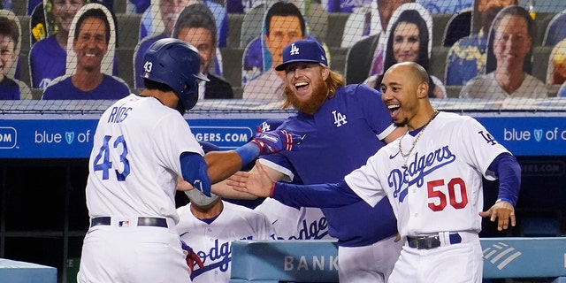 Los Angeles Dodgers' Edwin Rios (43) celebrates his solo home run with Justin Turner, sentrum, and Mookie Betts (50) during the eighth inning of the team's baseball game against the Oakland Athletics on Wednesday, Sept.. 23, 2020, in Los Angeles. (AP Photo/Marcio Jose Sanchez)