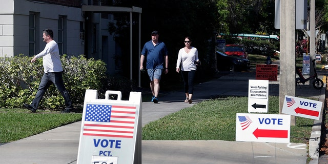 In this March 17, photo, voters head to a polling station to vote in Florida's primary election in Orlando, Fla. Florida felons must pay all fines, restitution and legal fees before they can regain their right to vote, a federal appellate court ruled Sept, 11. (AP Photo/John Raoux, File)