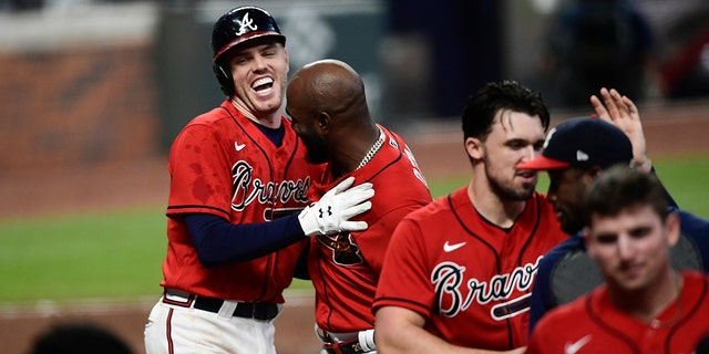 Atlanta Braves' Freddie Freeman, top left, celebrates his winning two-run home with teammates during the 11th inning of a baseball game against the Boston Red Sox, Vrydag, Sept.. 25, 2020, in Atlanta. (AP Photo/John Amis)