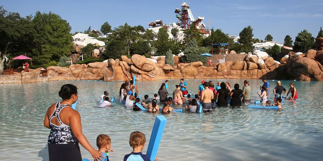 A woman and her sons at Disney's Blizzard Beach Water Park in June 2019. (Joe Burbank/Orlando Sentinel/Tribune News Service via Getty Images)