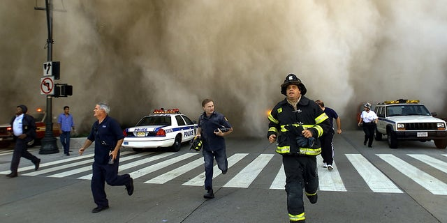 Policemen and firemen run away from the huge dust cloud caused as the World Trade Center's Tower One collapses after terrorists crashed two hijacked planes into the twin towers, 구월 11, 2001 뉴욕시. (Photo by Jose Jimenez/Primera Hora/Getty Images)