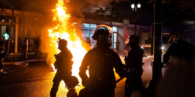 Portland police walk past a fire started by a Molotov cocktail thrown at police on September 23, 2020 in Portland, United States. (Photo by Nathan Howard/Getty Images)