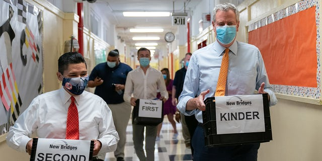 Richard Carranza, chancellor of the New York City Department of Education, left, and Bill de Blasio, mayor of New York, carry bins with supplies during a news conference at New Bridges Elementary School in the Brooklyn borough of New York, U.S., on Wednesday, Aug. 19, 2020. Photographer: Jeenah Moon/Bloomberg via Getty Images