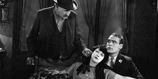 Actress Mabel Normand (1894-1930) gets her ear pulled by a possessive father in this scene from the 1923 film 'The Extra Girl'. Ralph Graves (1901-1977) sits next to her on the sofa.