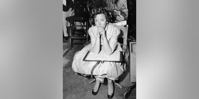 British actor and director Ida Lupino (1918 - 1995) sits in a director's chair with an open script on a film set, circa 1948.