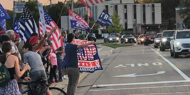 A pro-Trump group gathers Friday after an anti-Trump display was unveiled in Northbrook, Ill.