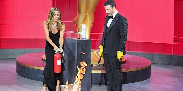 Jennifer Aniston puts out a fire in a wastebasket with Jimmy Kimmel at the 2020 Emmy Awards. (ABC/Image Group LA via Getty)