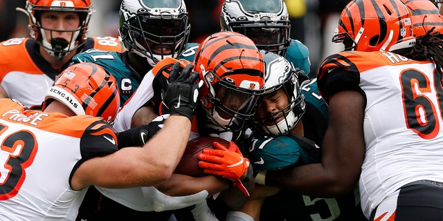 Cincinnati Bengals' Joe Mixon (28) is tackled by Philadelphia Eagles' Fletcher Cox (91) and T.J. Edwards (57) during the second half of an NFL football game, Sondag, Sept.. 27, 2020, in Philadelphia. (AP Photo/Laurence Kesterson)