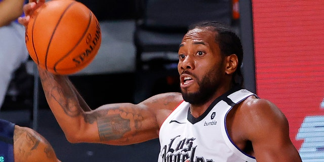 The Los Angeles Clippers' Kawhi Leonard grabs a rebound against the Dallas Mavericks during the second quarter of Game 4 of an NBA basketball first-round playoff series, Sunday, Aug. 23, 2020, in Lake Buena Vista, Fla. (Kevin C. Cox/Pool Photo via AP)