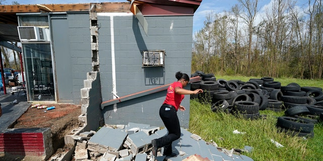 Layla Winbush walks over the debris of her family's destroyed auto detailing business in Lake Charles, La., in the aftermath of Hurricane Laura, Sunday, Aug. 30, 2020.