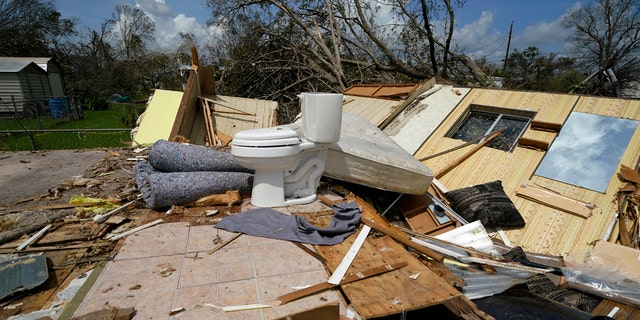 Remnants of the half destroyed mobile home of James Towfley, who is living in the standing half, are seen in Lake Charles, La., in the aftermath of Hurricane Laura, Sunday, Aug. 30, 2020.