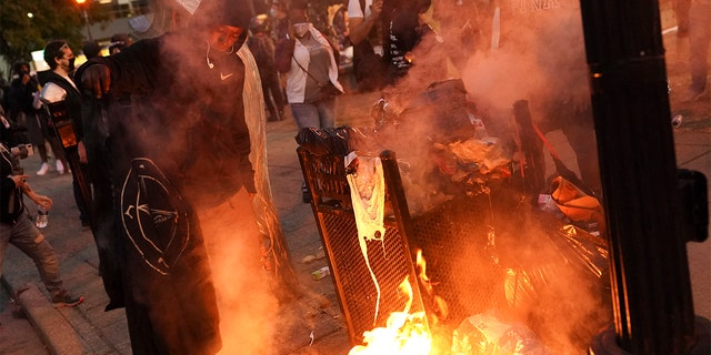A fire burns in downtown Louisville, Ky., after a grand jury indicted one officer on criminal charges six months after Breonna Taylor was fatally shot by police.(Associated Press)
