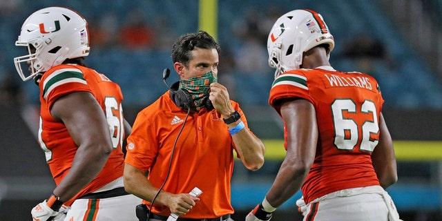 Miami coach Manny Diaz, center, walks on the field during an NCAA college football game against UAB in Miami Gardens, Fla., Thursday, Sept. 10, 2020. (Al Diaz/Miami Herald via AP)