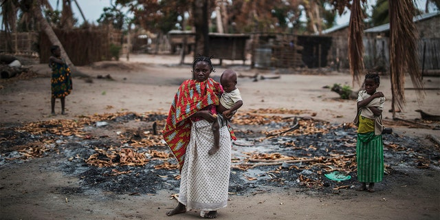 A woman holds her younger child while standing in a burned out area in the recently attacked village of Aldeia da Paz outside Macomia, on August 24, 2019. - On August 1, the inhabitants of Aldeia da Paz joined the long list of victims of a faceless Islamist group that has been sowing death and terror for nearly two years in the north of the country, which welcomes from September 4 the Pope. (Photo by MARCO LONGARI / AFP) (Photo by MARCO LONGARI/AFP via Getty Images)