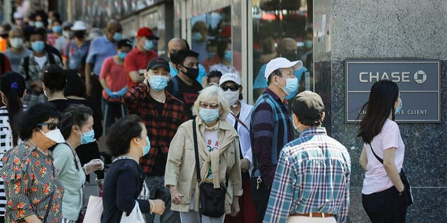 Patrons wearing protective masks wait to enter a Chase bank location, Monday, June 8, 2020, in the Flushing section of the Queens borough of New York. After three bleak months, New York City will try to turn a page when it begins reopening Monday after getting hit first by the coronavirus, then an outpouring of rage over racism and police brutality. (AP Photo/Frank Franklin II)