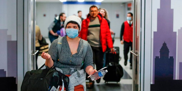 """Beginning Monday, travelers arriving from specific countries will no longer be required to undergo enhanced health screenings aimed at identifying passengers with COVID-19, as the current program """"has limited effectiveness because people with COVID-19 may have no symptoms or fever at the time of screening."""" In the above photo, taken in March, travelers are seen arriving at the international terminal of O'Hare International Airport in Chicago — one of the 15 designated airports for arriving international flights from the hardest-hit countires."""