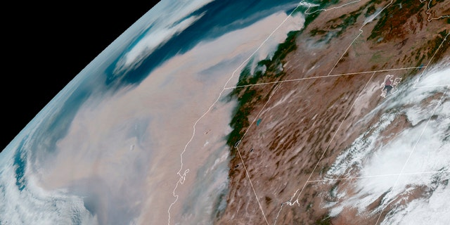 This GOES-16 GeoColor satellite image provided by the National Oceanic and Atmospheric Administration (NOAA), shows brown smoke from wildfires blowing westward in the atmosphere from California's Sierra Nevada to the Coast Ranges and from Oregon, top, on Wednesday, Sept. 9, 2020.