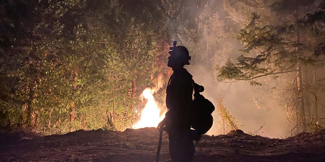 This photo provided by the Unified Fire Authority shows a Utah fire crew member on the scene working to protect the town of Butte Falls in southern Oregon.