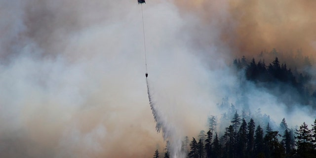In this Sept. 3, 2020, photo provided by the Opal Creek Ancient Forest Center, fire retardant is dropped at Jawbone Flats in the Opal Creek Wilderness in Oregon.
