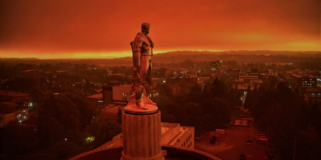 "This drone photo provided by Michael Mann shows the Oregon Capitol building, with its ""Oregon Pioneer"" bronze sculpture atop the dome, with skies filled with smoke and ash from wildfires as a backdrop in Salem, Ore., on Sept. 8, 2020."