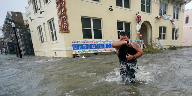 Trent Airhart wades through flood waters, Sept. 16, in downtown Pensacola, Fla.