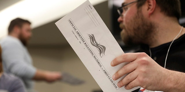 Election volunteer Tyler Jentoft-Johnson holds an absentee ballot as they're counted at the City Hall during the presidential primary election held amid the coronavirus disease (COVID-19) outbreak in Beloit, Wisconsin, U.S. April 7, 2020. REUTERS/Daniel Acker