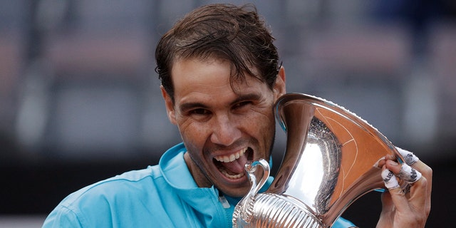 In this May 19, 2019 file photo, Rafael Nadal of Spain holds his trophy after winning against Novak Djokovic of Serbia at the end of their final match at the Italian Open tennis tournament, in Rome. (AP Photo/Gregorio Borgia)