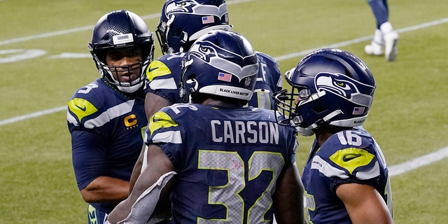 Seattle Seahawks running back Chris Carson (32) is greeted by quarterback Russell Wilson, 왼쪽, after Carson caught a pass from Wilson for a touchdown against the New England Patriots during the second half of an NFL football game, 일요일, 씨족. 20, 2020, 시애틀. (AP Photo/Elaine Thompson)