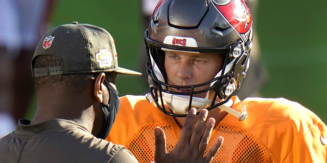 FILE - Tampa Bay Buccaneers quarterback Tom Brady talks to offensive coordinator Byron Leftwich during an NFL football training camp practice Friday, Aug. 28, 2020, in Tampa, Fla. (AP Photo/Chris O'Meara, File)